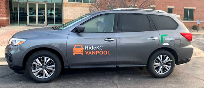 RideKC Vanpool in front of an office building. Gray SUV with white and orange lettering.